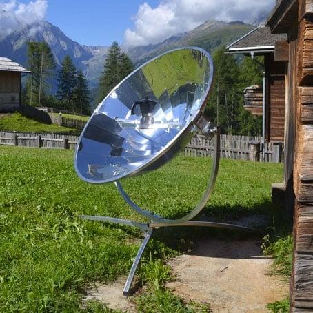 cuisinière solaire devant un chalet